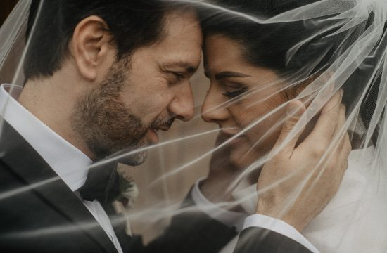 closeup of the bride and groom with the veil in front of the face
