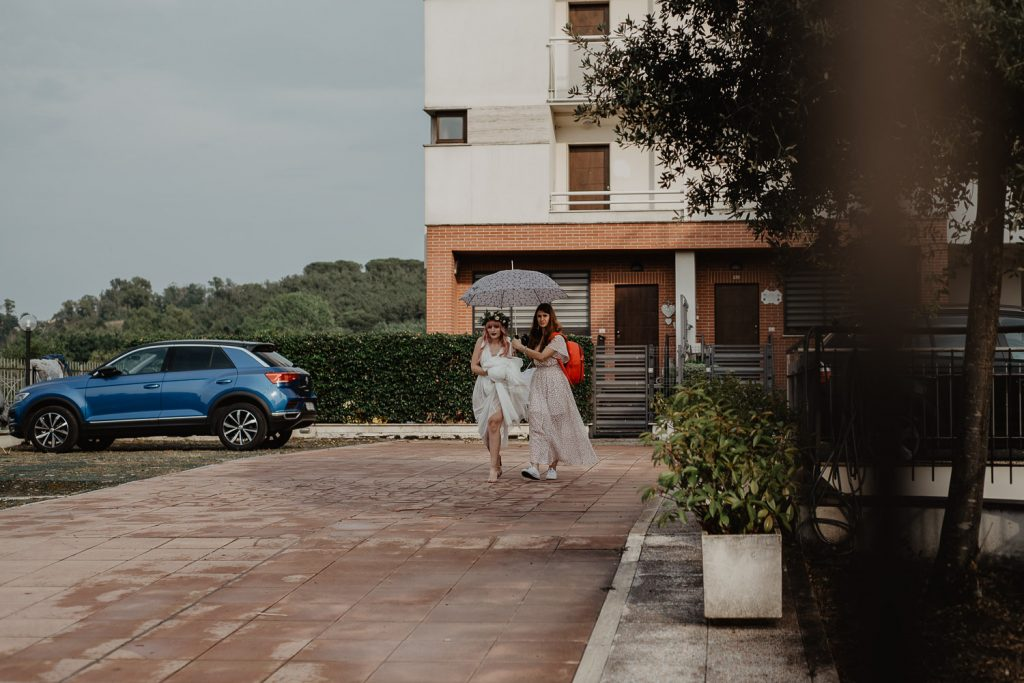 the bride and girl with umbrella leave the house