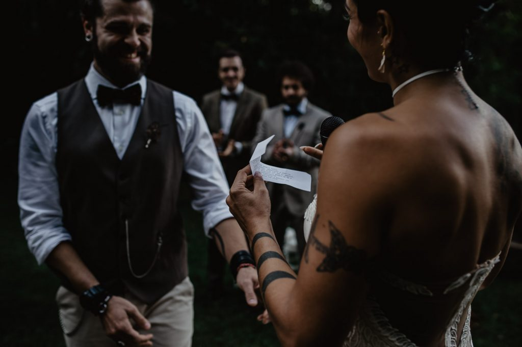 promises exchange between groom and bride during a wood wedding