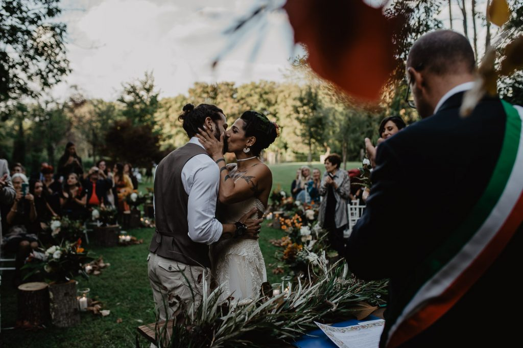 kiss between groom and bride during a wood wedding