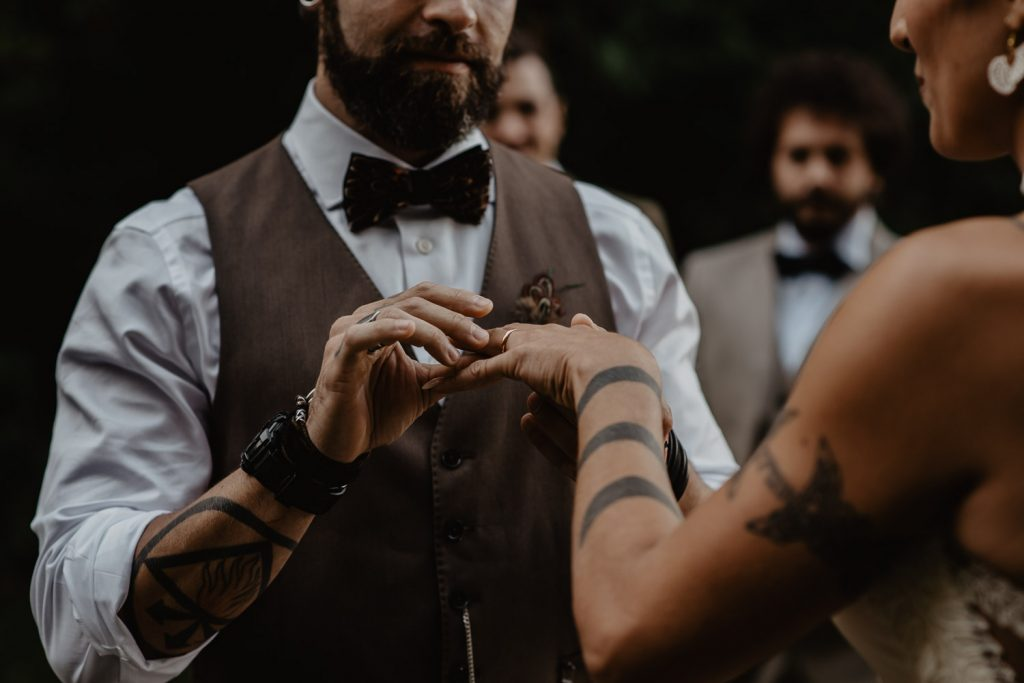 exchange of rings between groom and bride during a wood wedding