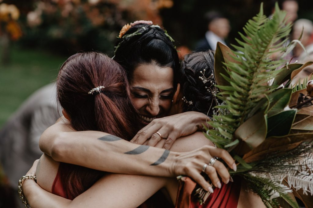embrace within bride and bridesmaids during a wedding