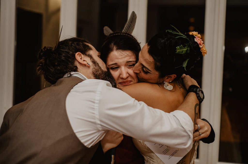groom and bride embrace the bridesmaid